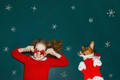 Curly girl and her friend dog, lies in green chalkboard with gre. Eting card for Merry Christmas. New year and holiday concept Royalty Free Stock Images