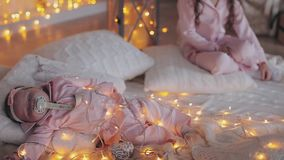 Curly girl and her newborn little sister together on white plaid knitted warm soft lights around them stock footage