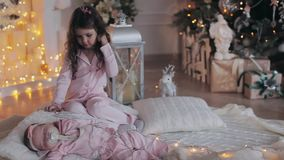 Curly girl and her newborn little sister together on white plaid knitted warm soft lights around them stock video