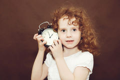 Curly girl holding alarm clock. Royalty Free Stock Photos
