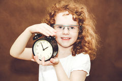 Curly girl holding alarm clock. Stock Photos