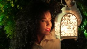 Curly girl with a lantern. Girl with a lantern looks at the light and frame. Young curly woman holding a lantern in her hand, inside of which a candle burns stock footage