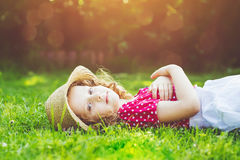 Curly girl lays on the grass in summer park. Background toning f Royalty Free Stock Image