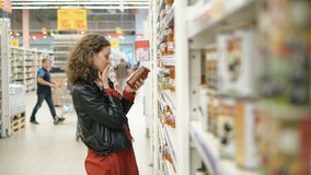 Woman carefully reads the composition of the product and is horrified in a hypermarket stock footage