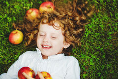 Curly girl lies on the grass with apple and smiling. Stock Photos