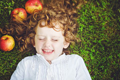 Curly girl lies on the grass Royalty Free Stock Image