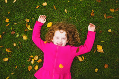 Curly girl lies on the grass and smiling. Stock Photos