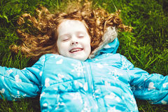 Curly girl lies on the grass and smiling Stock Photography