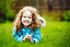 Curly girl lies on the grass and smiling Stock Images