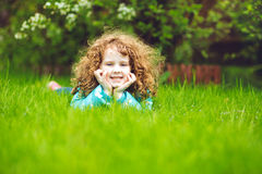 Curly girl lies on the green grass and smiling. Stock Photography