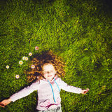 Curly girl lies on the green grass and smiling, toning photo. Stock Photography