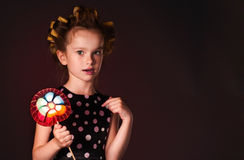 Curly girl with lollipop Royalty Free Stock Images