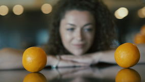 Curly girl looking on the oranges on table. Close-up. Camera focuses on two oranges on foreground. The camera moving from left to right. Beautiful curly girl stock video footage