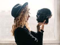 The curly girl looks in the eyes of the skull. Curly girl in a cap with a skull in her arms and a tattoo on her hand royalty free stock photo