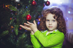 Curly girl near the Christmas tree Royalty Free Stock Photos