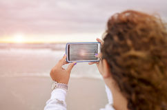 Curly girl photographing  the sunrise at the ocean. With her mobile phone, Lens flare effect Stock Photos