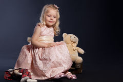 Curly girl in pink dress sitting on old suitcase Royalty Free Stock Image