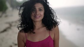 Curly girl posing outdoors. Charming smiling girl is walking under rain on the beach on the sea background. She is wearing a pink dress. Low aperture video stock video footage