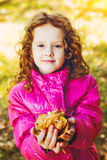 Curly girl in a red jacket with yellow autumn leaves in the hand Stock Photo