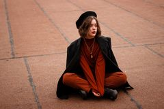 Curly girl in red pants and black hat sitting on the ground royalty free stock photos