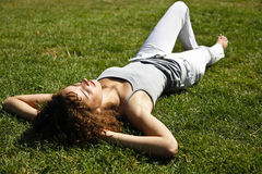 Curly Girl Relaxing On Grass. Cute Curly Girl Relaxing Lain Down On Grass Royalty Free Stock Images