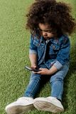Cute african american curly girl using smartphone royalty free stock image