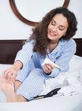 Curly girl rubbing cream in toes. Happy young woman in pyjamas rubbing cream into toes skin Stock Image
