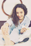 Curly girl rubbing cream in toes. Happy young woman in pyjamas rubbing cream into toes skin Stock Photo