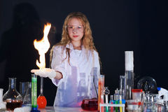 Curly girl shows science experiment in studio Royalty Free Stock Photo