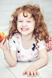 Curly girl smiling and eating a red apple Royalty Free Stock Image