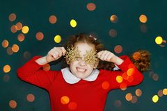 Curly girl with snowflakes in her eyes, lies on green chalkboard Royalty Free Stock Photo