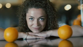 Curly girl take an oranges from table. Two oranges laying on the table. The girl is looking on fruits. Close-up face of a girl and oranges on a table. The girl`s stock video footage