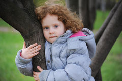 Curly girl on a tree in the park Royalty Free Stock Photo