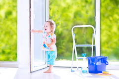 Curly girl washing a window in white room Stock Image