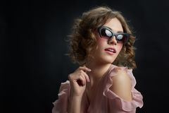 Curly girl wearing fashionable sunglasses. Stock Photo