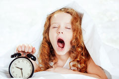 Curly girl yawn and holding alarm clock. Royalty Free Stock Image