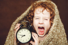 Curly girl  yawn and holding alarm clock. Royalty Free Stock Images