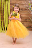 Curly girl in yellow gown with flowers royalty free stock images