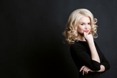 Curly gorgeous blonde woman in black blouse posing with crossed arms and holding finger on chin. Girl posing and smiling at camera Stock Photos