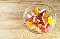 Curly gummies on a wooden table. Delicious gummies on a wooden table Royalty Free Stock Images