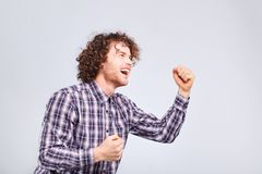 A curly guy is happy to raise his hands up. A curly guy is happy to raise his hands up against a gray background Stock Images