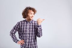 Curly guy with positive emotion on his face points with his fing. Er on the gray background Royalty Free Stock Photos