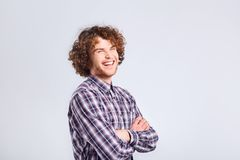 Curly guy smiles with a positive emotion. Curly guy smiles with a positive emotion up against a gray background Stock Photos