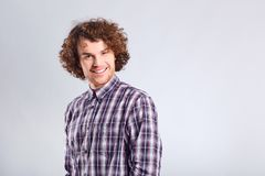 Curly guy smiles with a positive emotion. Curly guy smiles with a positive emotion up against a gray background Stock Images