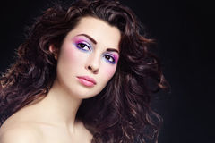 Curly hair. Portrait of young beautiful woman with long curly hair and fancy make-up stock image