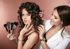Curly hair. Beauty makeup. Professional artist woman applying ha Stock Images