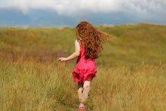 Curly hair girl run on the wheat field at sunset. Stock Photos