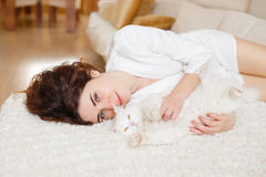 Curly hair girl in a white silk dressing gown in the early morning playing with white fluffy cat sitting on sofa Stock Photos