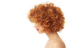 Curly hair. Profile portrait of young woman with beautiful red curly hair over wite background royalty free stock photo