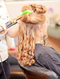 Curly hair styling. Woman getting hair curled at a salon royalty free stock images